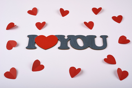 red hearts from paper on a white background around the inscription I love you. Valentines day