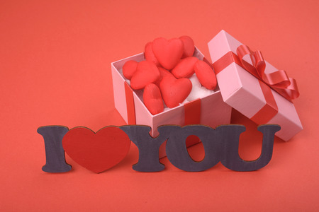 Valentines day. Pink gift box and plate i love you on red background.
