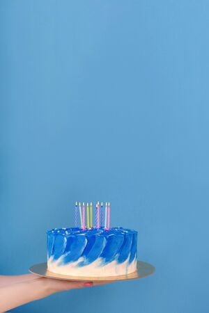 Girls hands are holding beautiful and tasty cake with white and true blue color cream with holiday candles on a blue background with place for text.