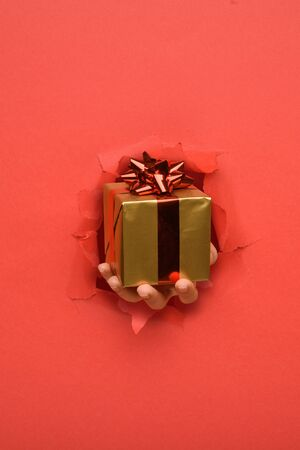 Hand give gold gift box with red ribbon on torn red paper wall. Copy space aside for your advertising and offer or sale content.