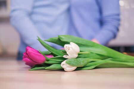 Flowers tulips lie on the table against the background of a young couple holding hands, Valentines Day holiday, a loving couple