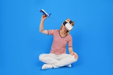 Young girl in virtual reality VR glasses. holding model airplane. It looks like it is flying in sky against blue background of innovative technologies and concept of education and entertainment
