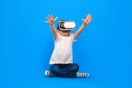 Boy in virtual reality glasses VR holds his hands in front of him and tries to play with virtual world, wearing white t-shirt, denim pants on blue background. Innovative technology, education concept