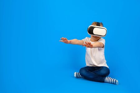 Boy in virtual reality glasses VR holds his hands in front of him and tries to play with virtual world, wearing white t-shirt, denim pants on blue background. Innovative technology, education concept Stock Photo