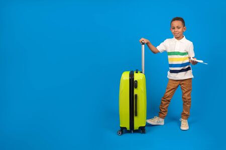 African-American traveler boy is ready for the trip, showing passport and plane tickets is happy, yellow travel bag, has a special offer from a travel company, on a blue background.