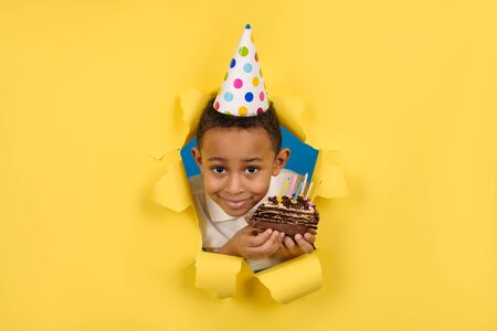 Happy African-American boy celebrates birthday by holding a chocolate cake in his hands with candles and enjoying holiday on yellow torn paper background. Concept party birthday, space for copy