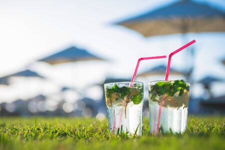 Refreshing fresh alcoholic cocktails Mojito with mint ice and lime stand on lawn with grass against the background of the beach and umbrellas, loungers for recreation