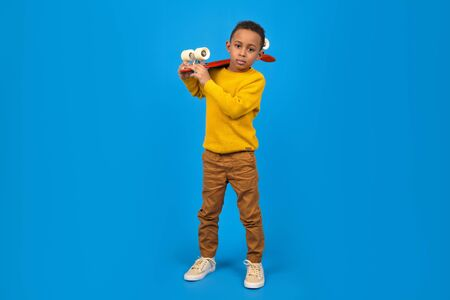 Funny little African-American boy with a skateboard smiles and looks away, standing on a blue background. Concept of activity and happy childhood