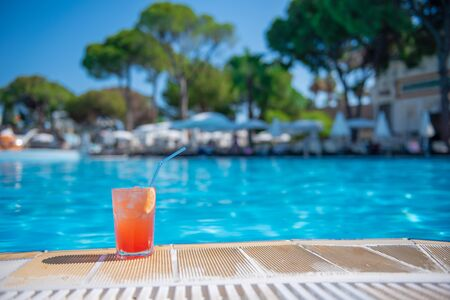 Fresh alcoholic red cocktail on beach with ice in glass on edge of pool in summer weather against background washed up pool and recreation area. Concept good holiday and travel, place for text Archivio Fotografico