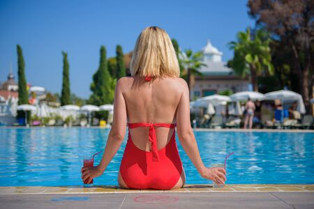 Beautiful young girl in red bathing suit is relaxing by pool with cosmopolitan and mojito cocktail, girl is sitting on edge of pool skin on background of blurred pool. Conception luxury and travel Standard-Bild