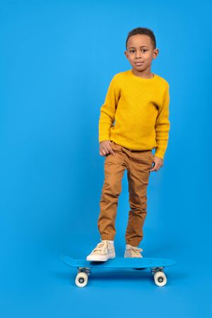 Funny little African-American boy with a skateboard smiles and looks away, standing on a blue background. Concept of activity and happy childhood.