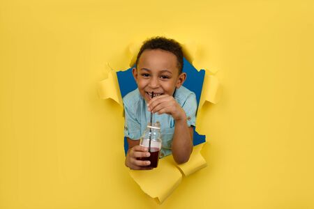 Happy cheerfully smiling African-American boy holds bottle of juice, drinks red cherry drink from black bar straw, against torn paper wall background. Detox healthy drink concept with space for text Banco de Imagens