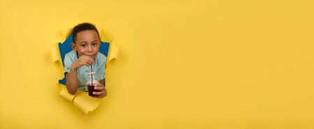Happy African-American boy in blue shirt is holding juice bottle, drinking red cherry drink from black bar straw, against yellow background of torn paper wall. Healthy drink detoxification concept.