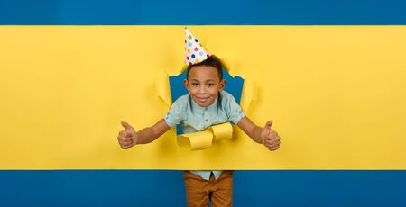 Ð¡heerful and happy birthday boy African-American with cone cap on his head against ragged paper yellow background of wall, reaching out to hold something or take it, asks to pick it up.