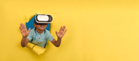 African-American boy in virtual reality headset VR. Immersed in virtual 3d world, touches virtual objects, interacts with computer world, on yellow torn paper background with space for text