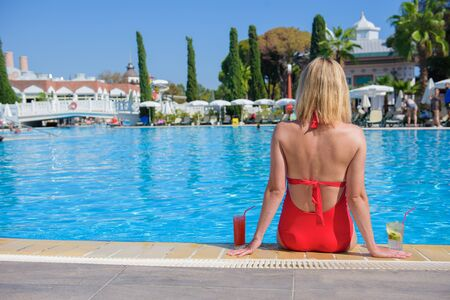 Beautiful young girl in red bathing suit is relaxing by pool with cosmopolitan and mojito cocktail, girl is sitting on edge of pool skin on background of blurred pool. Conception luxury and travel