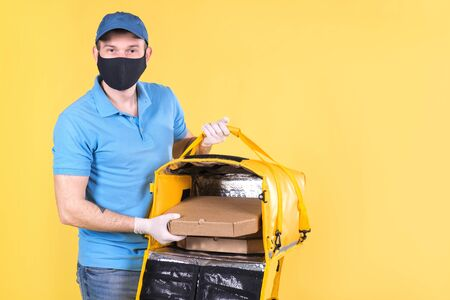 Courier wearing virus protection mask and medical food delivery gloves with yellow open thermos bag holds out an order from restaurant for customer on yellow studio background. safe delivery of food