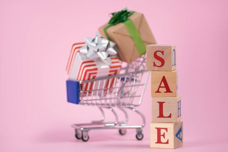 Red word SALE laid out wooden cubes with supermarket grocery cart full of gift boxes on pink background with space for text. Concept of selling products in supermarket or online store on Black Friday
