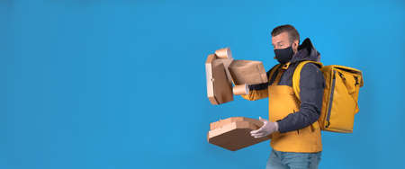 Food delivery man in yellow uniform, wearing mask and gloves, slipped, lost his balance, and hurled box of food from restaurant. Clumsy food vendor tore up customers order. Poor product delivery