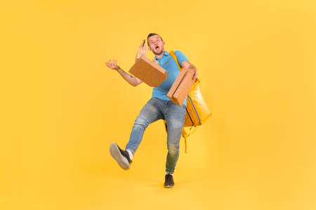 Delivery guy in blue uniform slipped and lost his balance and threw boxes of food from restaurant in direction. Clumsy food delivery guy broke up an order for customer. Poor product delivery Imagens