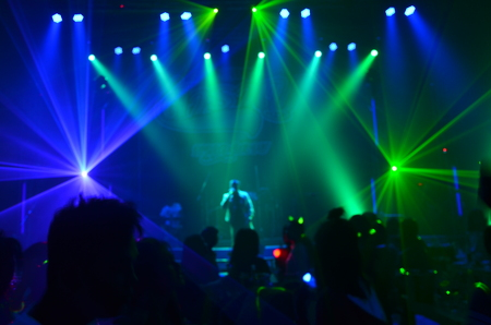 silhouette concert in front of stage.Defocused entertainment concert lighting on stage, blurred disco party. Stock Photo