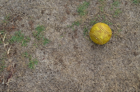 beat the competition: old softball in field Stock Photo