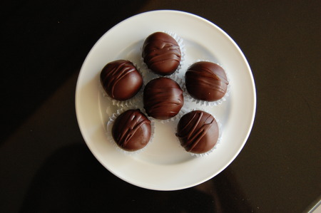 chocolate truffles: Assorted dark chocolate truffles with cocoa powder, coconut and chopped hazelnuts on a dessert plate