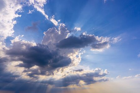 Blue sky with clouds and sun reflection,Sun beams or rays breaking through the dark clouds at sunset. Hope, prayer, Gods mercy and grace. Beautiful spectacular conceptual meditation background.