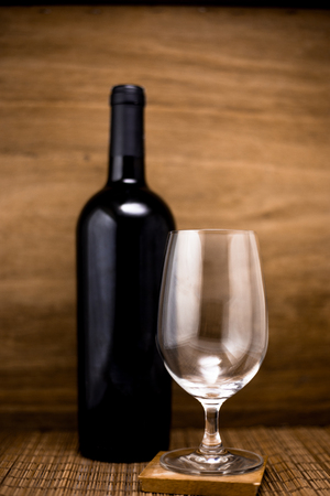 Wine bottle with glass on wooden background,empty glass and alcohol bottle
