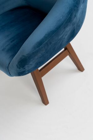 blue velor chair with wooden legs on a white background