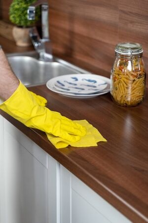 in the kitchen they wipe the table in yellow gloves. wipe the table with a rag.