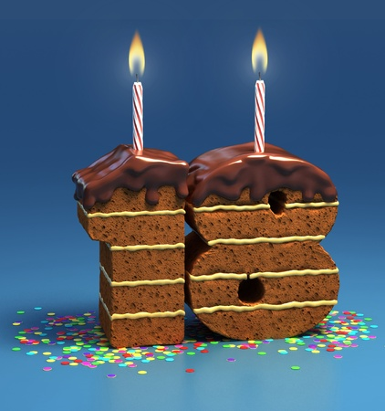 Chocolate birthday cake surrounded by confetti with lit candle for a eighteenth birthday