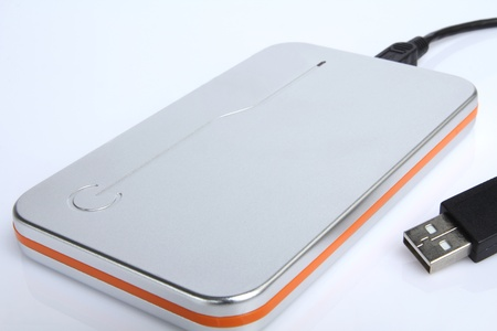 hard drive external silver and orange color for storage. photo