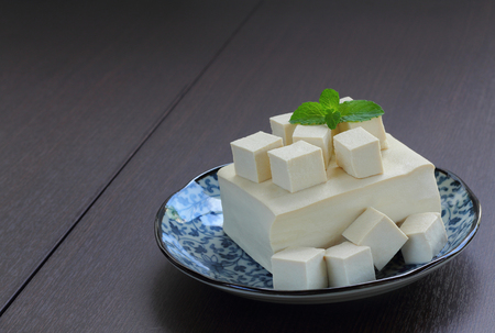 Tofu fresh is raw food with vegetarian food, wood background.