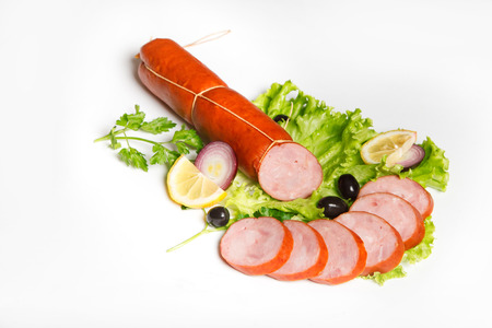 veal sausage: Still Life with sausages, salami and ham on a wooden table isolated on white background. Stock Photo