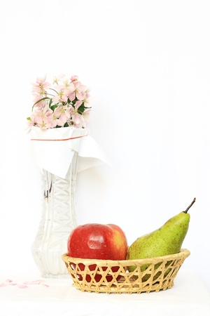 basket with apple, pear and vase with flower photo