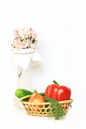 basket with onion, pepper bulgarian, tomato, dill and vase with flower photo
