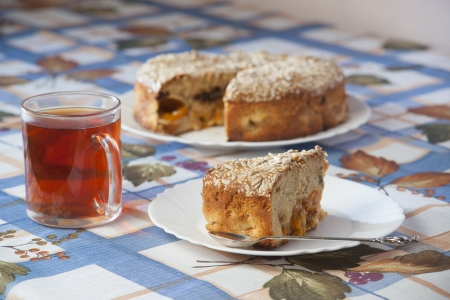 Apricot pie on plate and cup with tea. High resolution photo