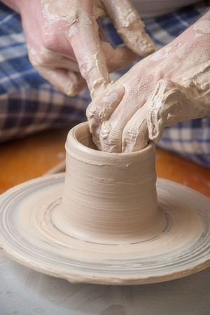 craftswoman: Hands of a potter, creating an earthen jar on the circle Stock Photo