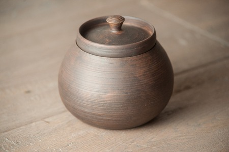 handcrafted: Traditional handcrafted brown pot with a cap Stock Photo