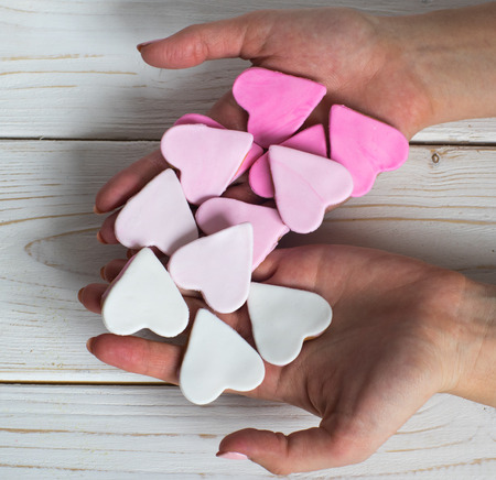 handbreadth: Pink cookies in woman hands, heart shape, white background