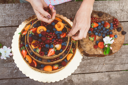 carefully: Woman hands of baker carefully decorate cheesecake with fruits and berries on the old planks, white apple and cherry flowers Stock Photo