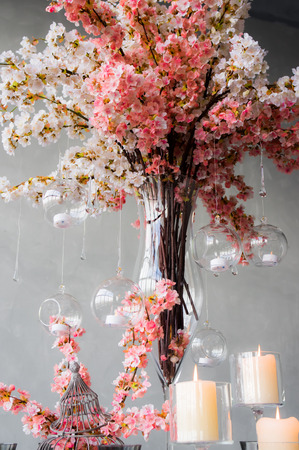 Wedding decoration for banquet with sakura,  candles and glass drops