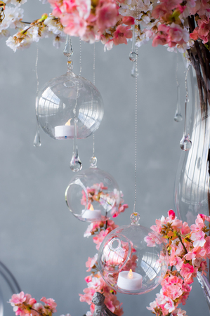 Wedding decoration for banquet with pink sakura, candles, glass drops Stock Photo