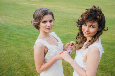 pessoas: Two beautiful brides holding hands on the green field of the golf club