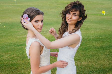 correcting: Two beautiful brides correcting hair on the green field of the golf club