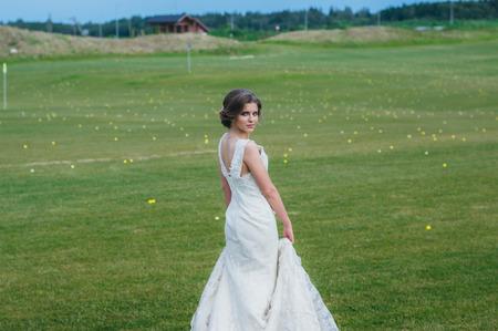 club dress: Beautiful bride in wedding dress on the green field of the golf club Stock Photo