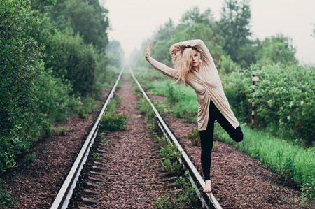 Portrait of young girl on railroad in motion with hands on head Stock Photo