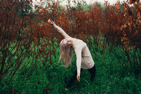 Portrait of young girl dancing between dead trees, in motion