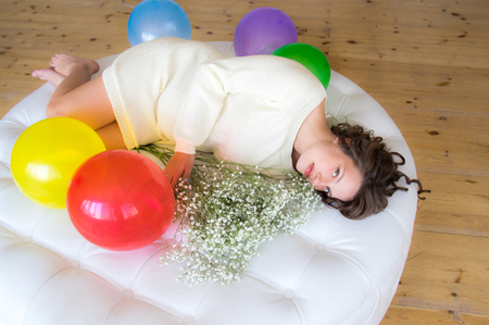 Pregnant woman in white dress lies on round sofa with bouquet of flowers Stock Photo